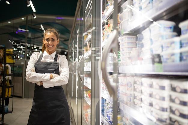 판매를위한 냉동 생선을 준비하는 슈퍼마켓 노동자 무료 사진