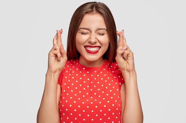 Суеверная женщина с красной помадой позирует у белой стены Бесплатные Фотографии