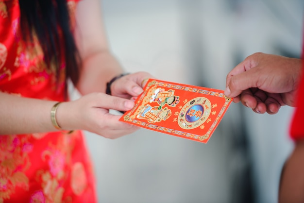 The supervisor give ang pao a gift for chinese new year with a beautiful asian woman. Premium Photo