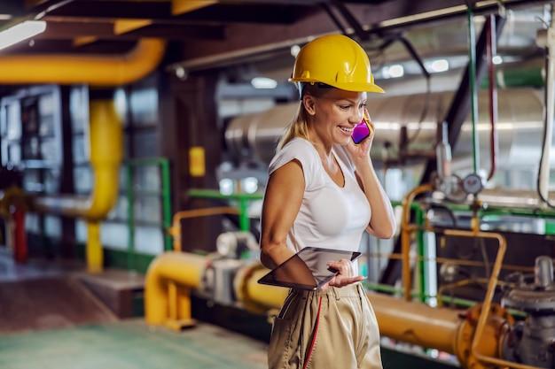 공장 난방에 서있는 동안 태블릿을 들고 전화 대화를하는 감독자. 프리미엄 사진