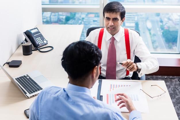 Supervisor talks to subordinate professional in office building Premium Photo