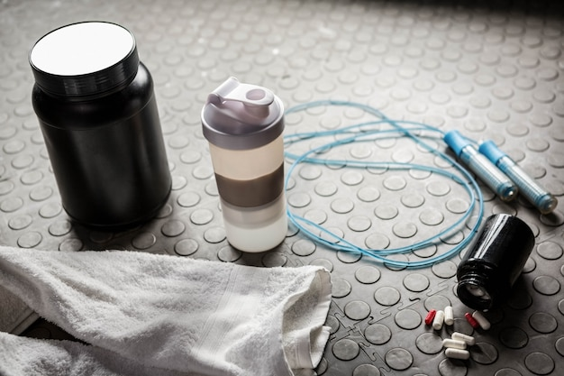 Supplements and rope on the floor at the crossfit gym Premium Photo