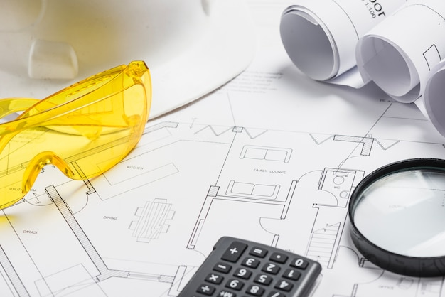 Supplies and glasses with blueprints Free Photo
