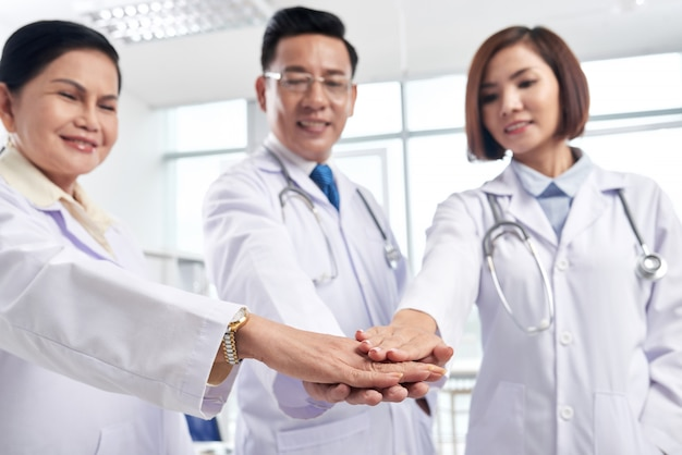 Supportive medical coworkers stacking hands to show collaboration is the key to success Free Photo