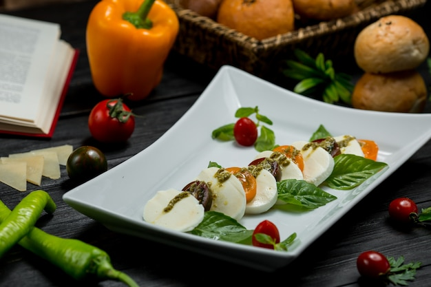 A suqare plate of chopped mozarella cheese, cherries and mint leaves. Free Photo