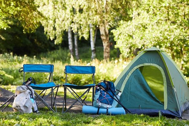 숲에서 캠핑 사이트에 빈 텐트와 캠핑 장비의 표면 이미지, 복사 공간 프리미엄 사진