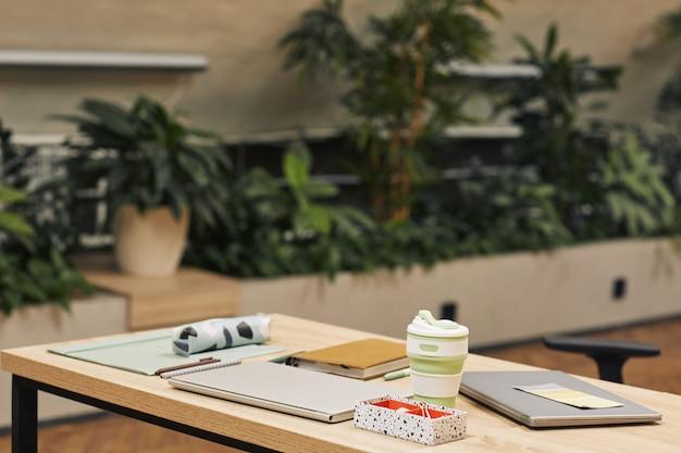 식물로 장식 된 현대 대학 도서관의 표면 이미지, 전경에서 용품을 공부하는 직장에 초점, 복사 공간 프리미엄 사진