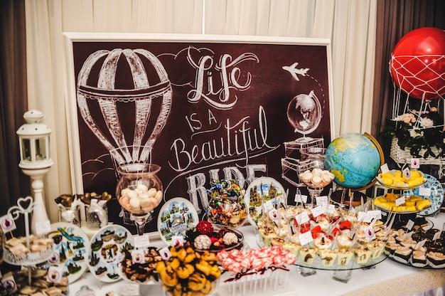 表面-人生は美しいです。結婚式のテーマ-ツアー、旅行、グローブ。お菓子とカラフルなテーブル。キャンディービュッフェでおいしいお菓子。パーティーのデザートテーブル。ケーキ、カップケーキ。 Premium写真