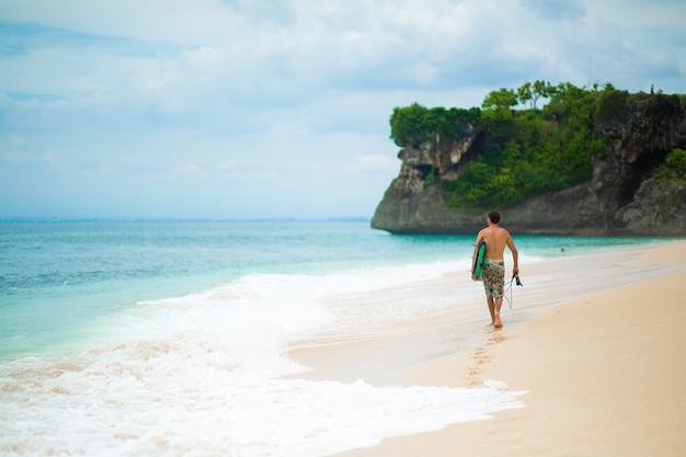 Серфер. серфинг человек с доской для серфинга, идущий на песчаном тропическом пляже. Premium Фотографии