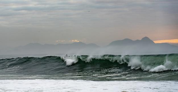 Surfista sulle onde dell'oceano nella spiaggia di copacabana Foto Gratuite