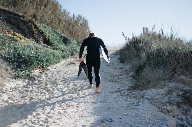 Серфер с ластами и бордюром в гидрокостюме на берегу океана Premium Фотографии