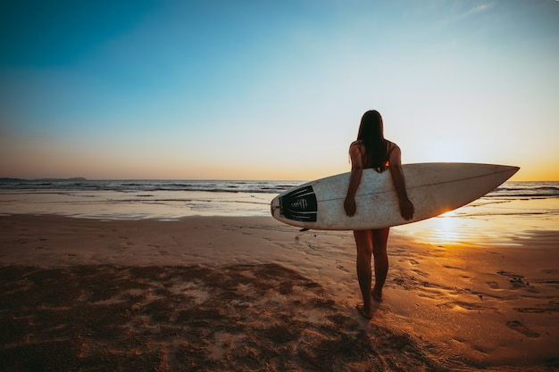 Surfer woman in bikini go to surfing. silhouette of beautiful sexy woman with surfboard on beach at sunset. Premium Photo