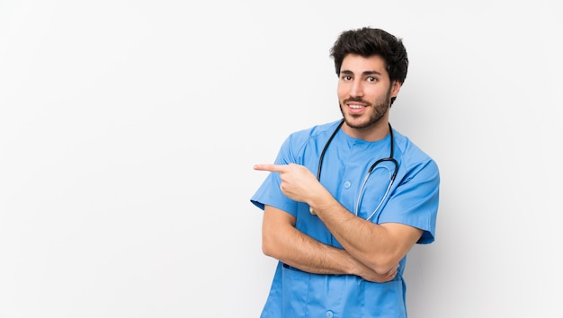 Surgeon doctor man over isolated white wall pointing finger to the side Premium Photo