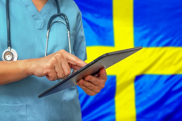 Surgeon or doctor using a digital tablet on the background of the sweden flag Premium Photo