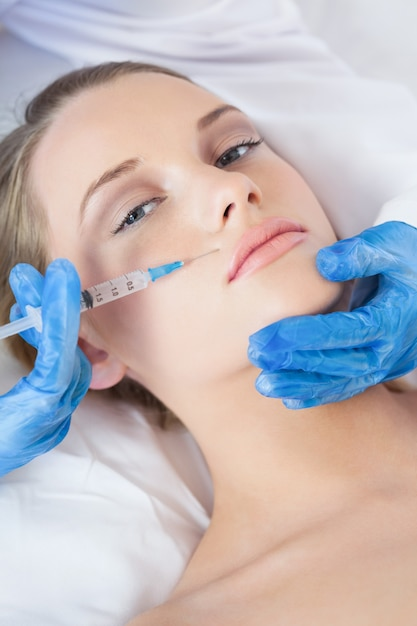 Surgeon making injection bove lips on pretty woman lying Premium Photo