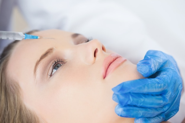 Surgeon making injection on forehead on calm woman lying Premium Photo