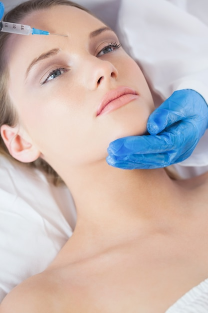 Surgeon making injection on forehead on relaxed woman lying Premium Photo