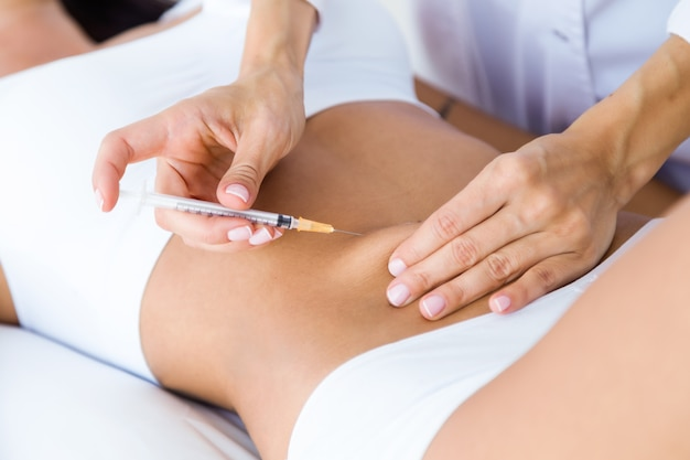 Хирург делает инъекцию в женский организм. концепция липосакции. Бесплатные Фотографии