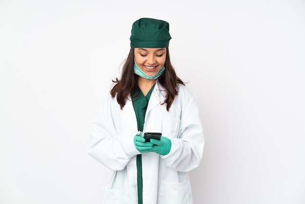 Surgeon woman in green uniform on white wall sending a message with the mobile Premium Photo