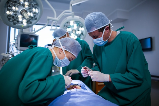 Surgeons performing operation in operation theater Free Photo