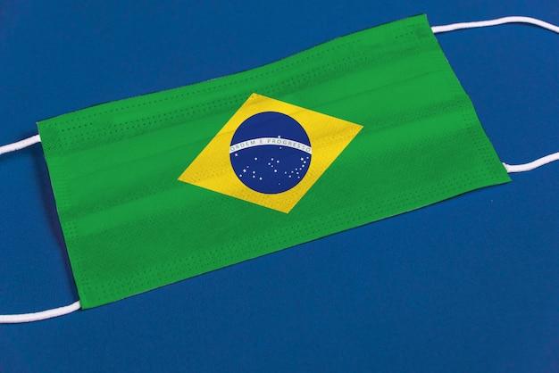 Maschera chirurgica su sfondo blu con bandiera brasiliana Foto Gratuite