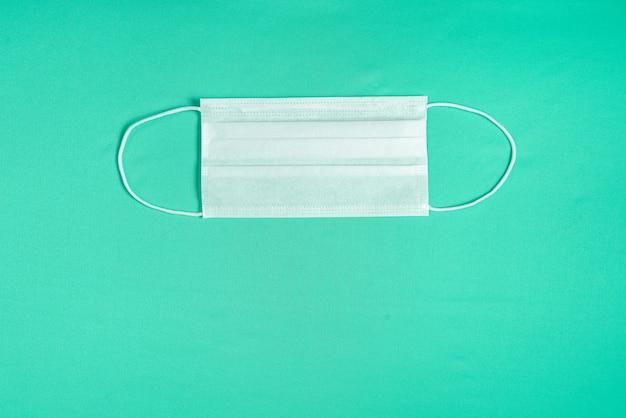 Хирургическая маска на минималистском зеленом фоне Бесплатные Фотографии