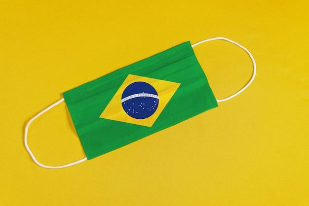 Maschera chirurgica su sfondo giallo con bandiera brasiliana Foto Gratuite