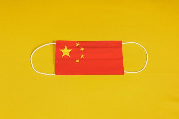 Maschera chirurgica su sfondo giallo con bandiera della cina Foto Gratuite
