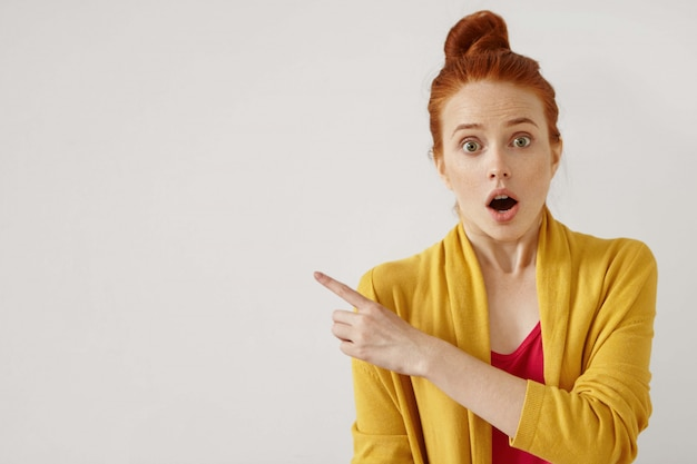 Surprise and astonishment concept. human feelings and reaction. portrait of shocked amazed young caucasian ginger woman pointing index finger sideways Free Photo