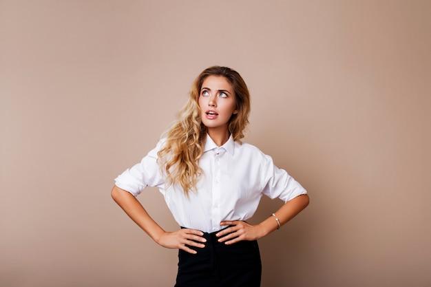 Volto a sorpresa. donna bionda in attrezzatura casuale che controlla parete beige. ragazza uscita alla ricerca. Foto Gratuite