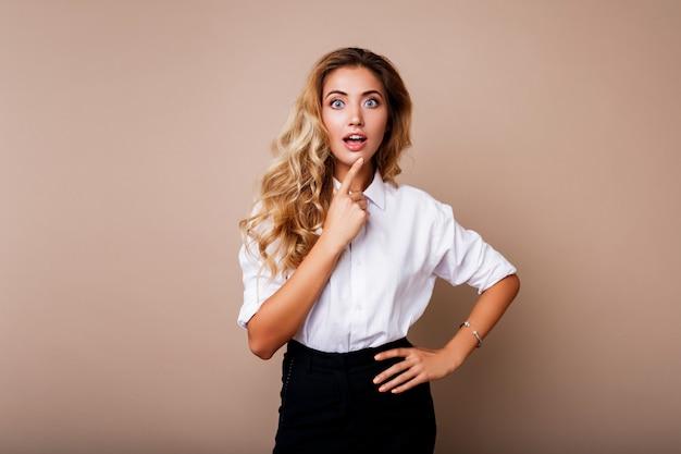 驚きの顔。ベージュの壁の上に立っているカジュアルな服装の金髪の女性。探している女の子が終了しました。 無料写真