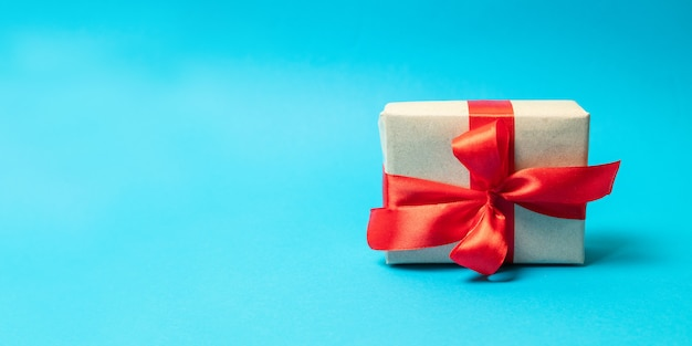 Surprise gift wrap with red ribbon bow on a blue background. happy birthday Premium Photo