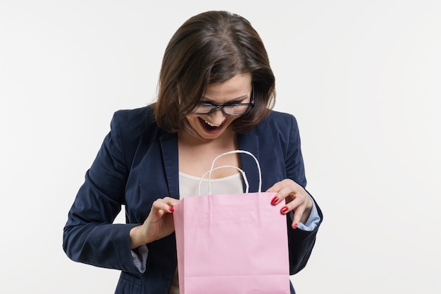 Surprised adult woman looking shopping bag Premium Photo
