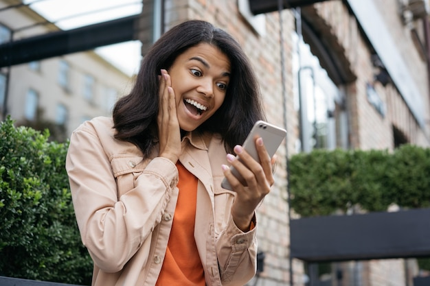 Surprised african american woman using mobile phone, looking at digital screen, she winning online lottery, celebration success Premium Photo