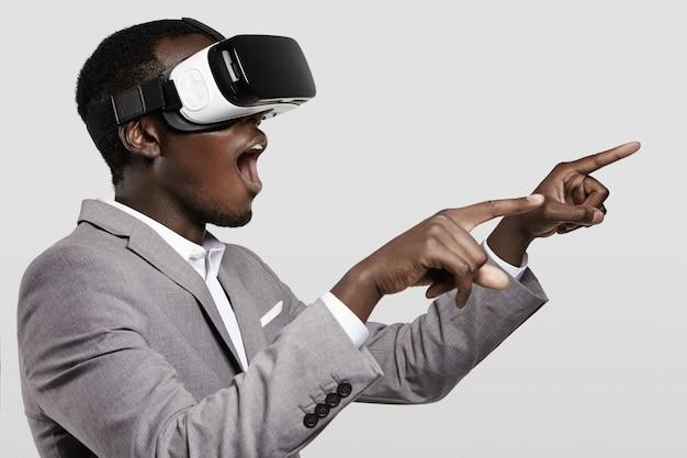 Uomo d'affari africano sorpreso che utilizza l'auricolare oculus rift, sperimentando la realtà virtuale durante la riproduzione di un videogioco. Foto Gratuite