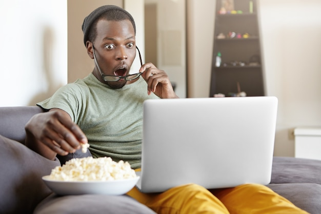 Surprised african male sitting on couch at home, eating popcorn and watching exciting tv show online on laptop computer or shocked with cliffhanger ending of detective series, keeping his mouth open Free Photo