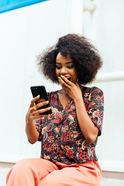Surprised african woman, covering her mouth by hand while looking at smartphone screen Free Photo