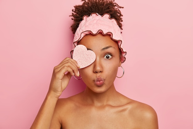 Surprised afro woman covers one eye with cosmetic sponge, keeps lips rounded, bugged eyes, has beauty treatments in spa salon, has combed curly hair Free Photo