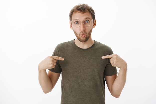 Surprised and amazed creative guy with bristle in glasses and dark-green t-shirt pointing at himself folding lips from interest and curiosity being picked by boss Free Photo