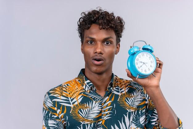 白地に青の目覚まし時計を保持している葉のプリントシャツの葉に巻き毛の驚きと混乱の若いハンサムな浅黒い男 無料写真