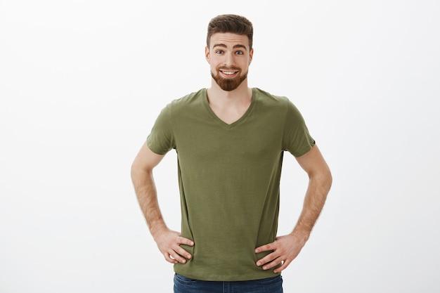 Удивленный и восторженный красивый спортивный бородатый парень в футболке, держащий руки на бедрах и улыбающийся, поднимающий брови от веселья и изумления, расслабленно позирует над белой стеной Бесплатные Фотографии