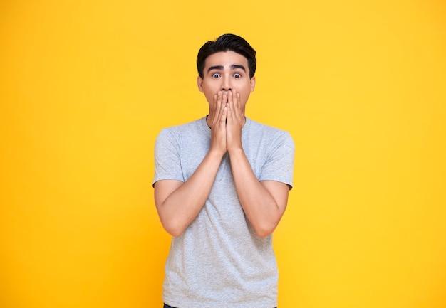 Удивленный и шокированный азиатский мужчина, закрывающий рот руками, изолированными на ярко-желтом фоне. Premium Фотографии