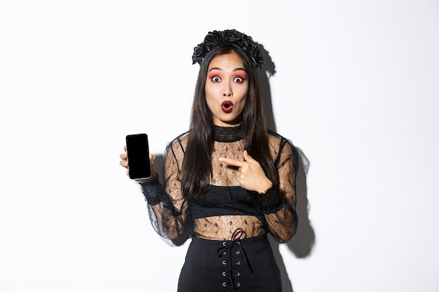 Surprised asian girl in black gothic dress with wreath, gasping amused and pointing finger at mobile phone display, showing halloween banner or promo, standing over white background. Free Photo