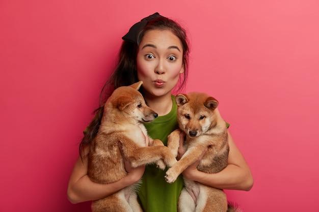 驚いたアジアの女性は唇を折りたたんで、2匹の子犬とポーズをとり、獣医クリニックに運びます。 無料写真