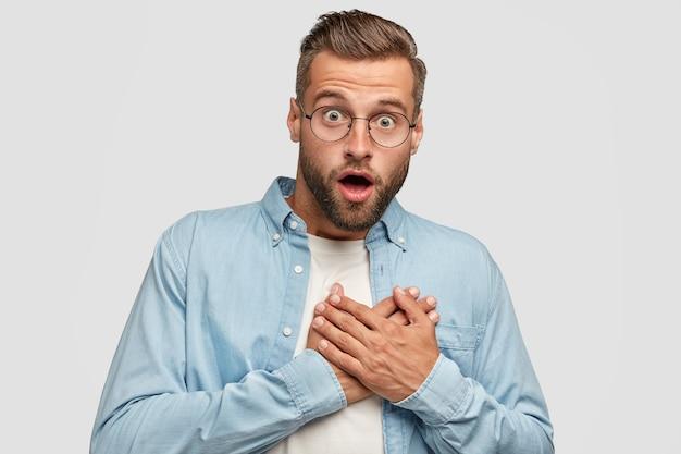 Удивленный бородатый парень позирует у белой стены Бесплатные Фотографии