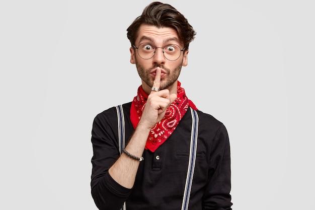 驚いたひげを生やした男は、静かなジェスチャーをし、人差し指で唇に触れ、白い壁に隔離されたサスペンダーと赤いバンダナ付きのスタイリッシュなシャツを着ています 無料写真