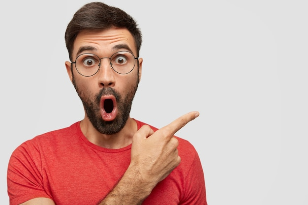 Surprised bearded young male with eyes popped out, has astonished expression, points aside at blank copy space Free Photo