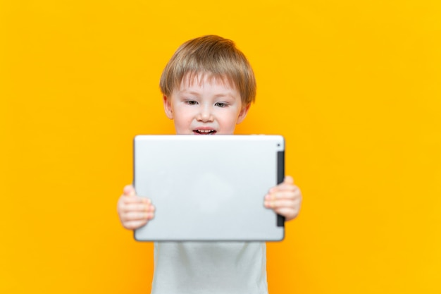 Surprised blonde three years old boy with his mouth open surprised, holding in his hands a tablet pc and looking at the camera Premium Photo