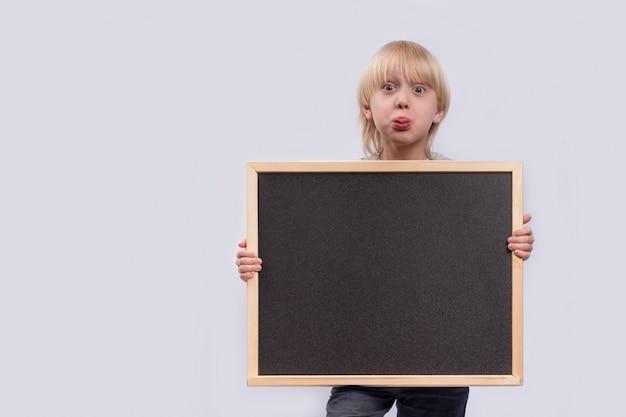 黒板を持って驚いた少年。黒のコピースペース。テンプレート。モックアップ Premium写真