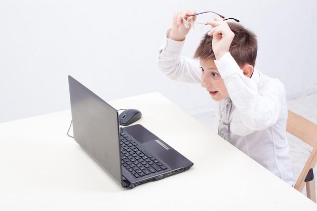 Il ragazzo sorpreso utilizzando il suo computer portatile su sfondo bianco. Foto Gratuite